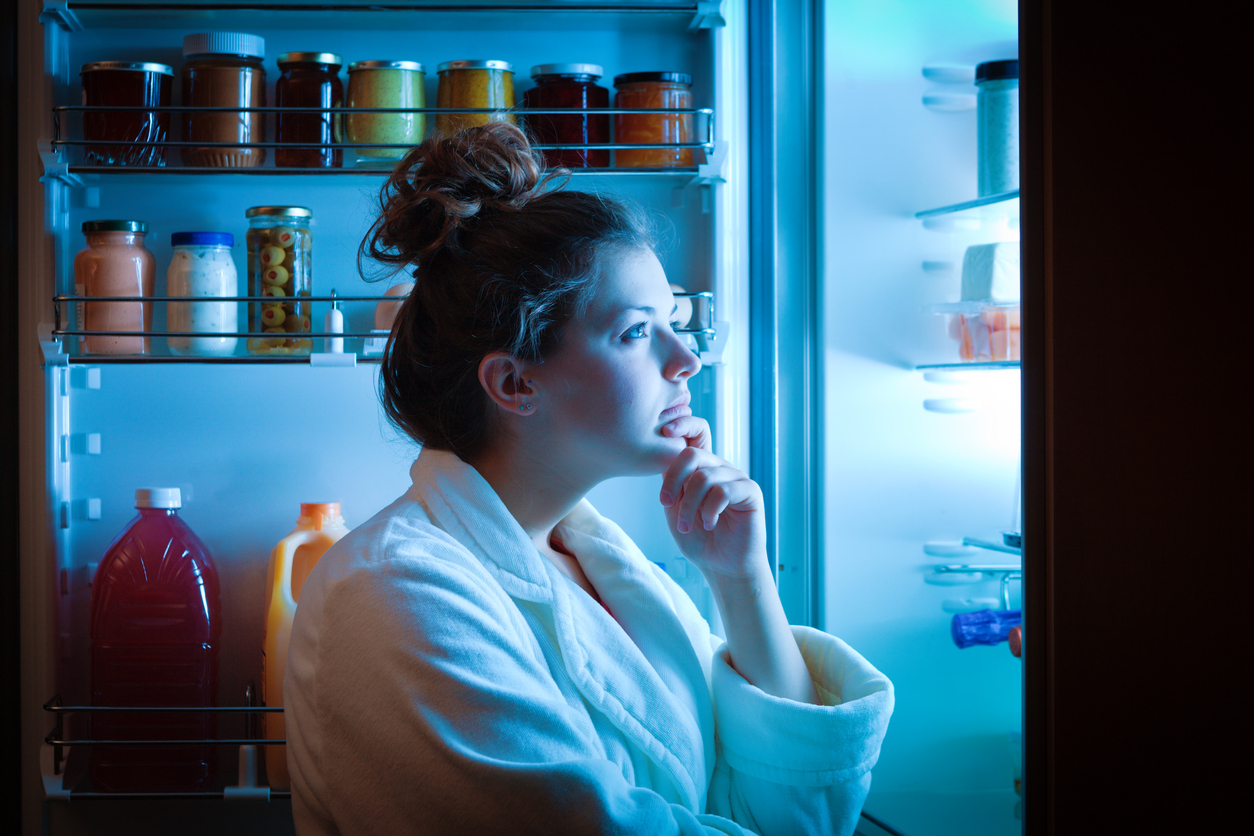 young woman in front of fridge at night