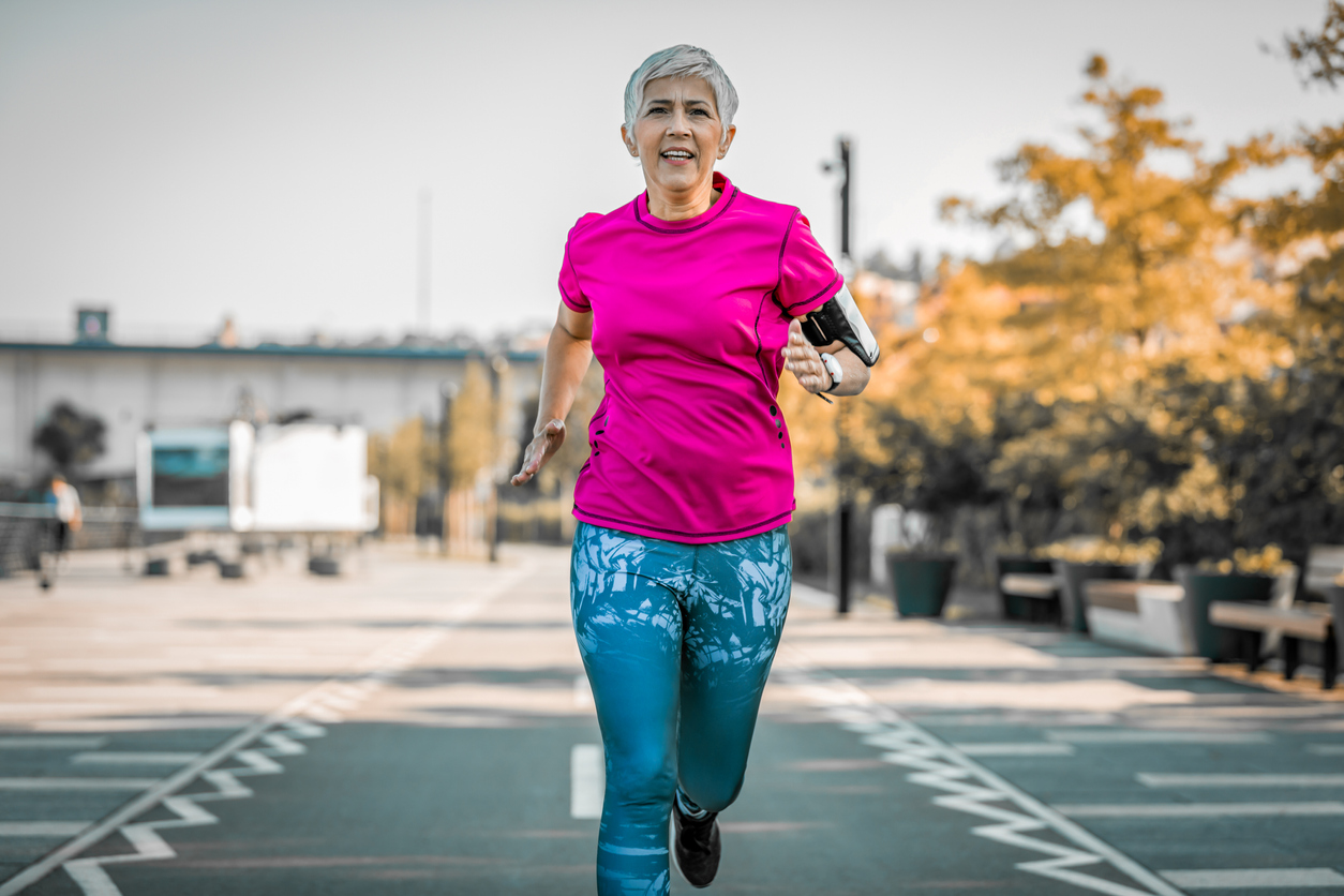 Senior woman jogging on track wearing pink shirt