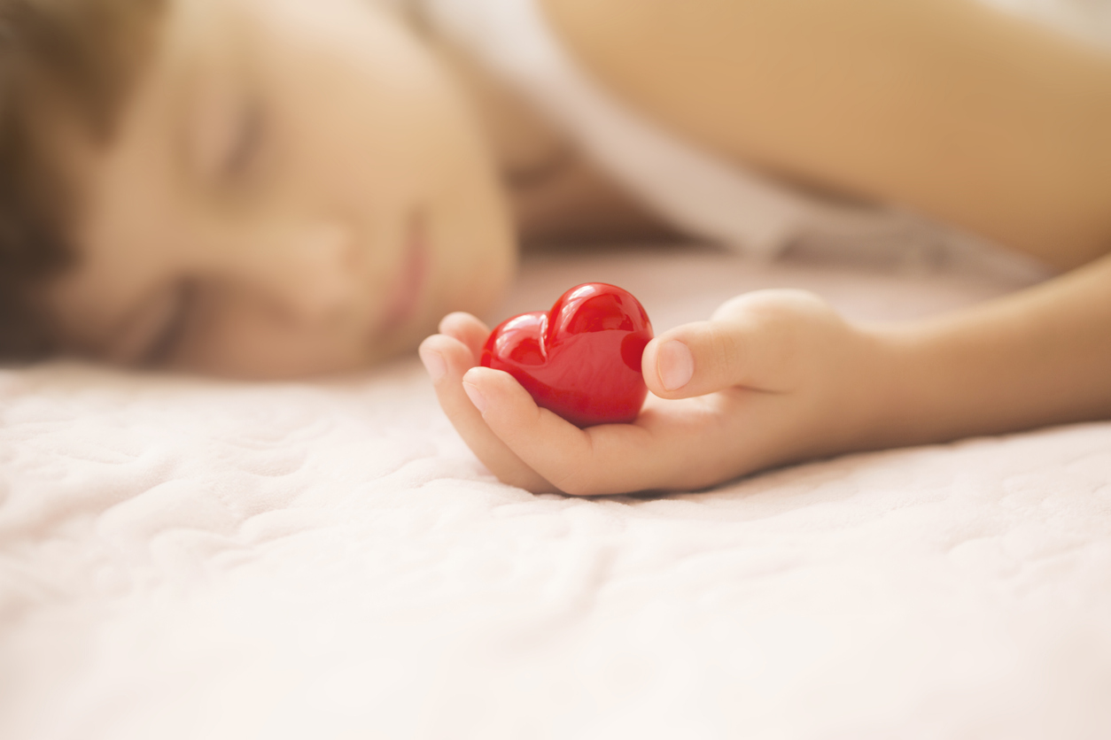 little girl sleeping with red heart in her hands
